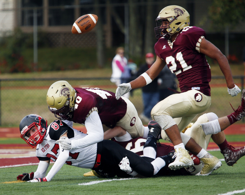 Greg Ruff of Thornton Academy keeps his eye on the football after Griffin Madden of Scarborough fumbled. Rome Pura makes the tackle.