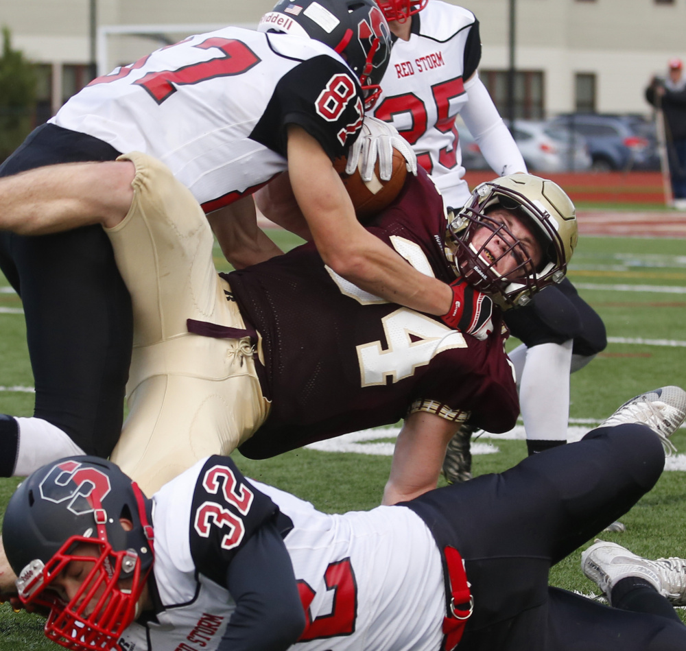 Owen Elliott of Thornton Academy finds little running room in the third quarter while being brought down by Griffin Madden of Scarborough.