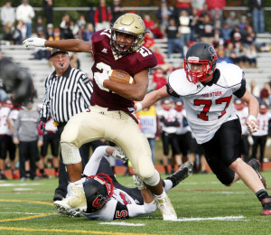 Greg Ruff, who gained 227 yards on 30 carries for Thornton Academy, tries to avoid Mahlon Glidden, right, and Connor Kelly of Scarborough during the first quarter of Thornton's 48-7 victory Saturday.