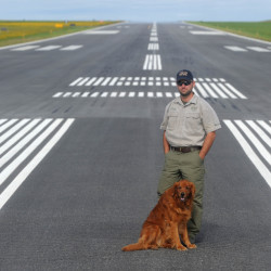 Randy Marshall, airport manager at Robert LaFleur Municipal Airport, stands with his dog Molly on the newly renovated runway at the city-owned airport in Waterville.