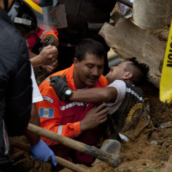 A worker is rescued after he was trapped at the site of a mudslide in Cambray, near Guatemala City, on Saturday. The hill that towers over Cambray collapsed late Thursday.