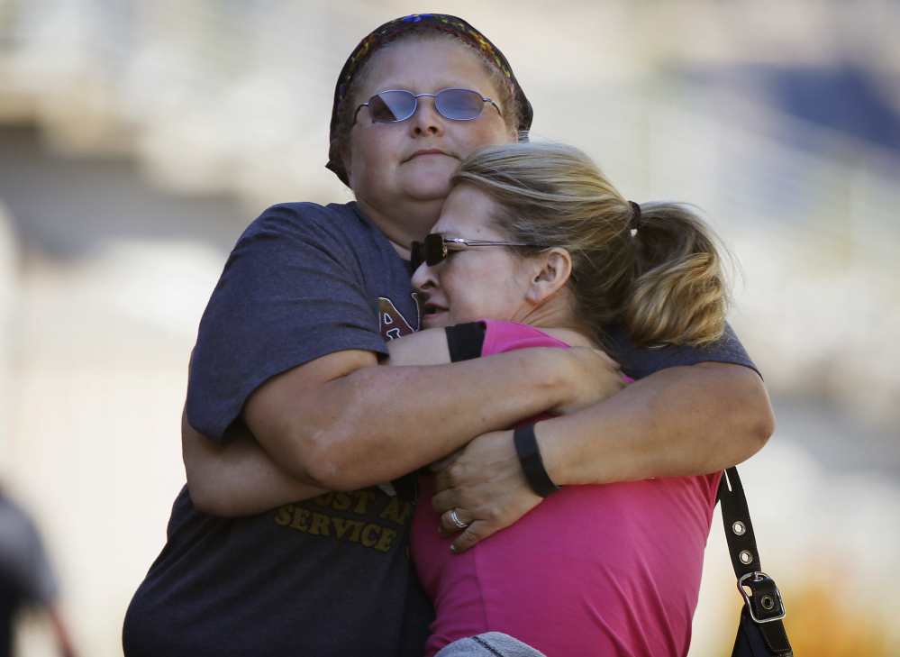 People embrace while preparing to get driven to Umpqua Community College to collect belongings Friday in Roseburg, Ore.