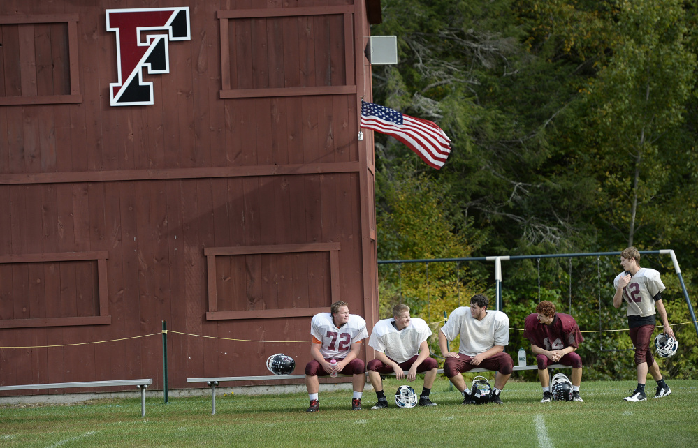 "Freeport High football players – from left, Tucker Ginn, Edward Lefebvre, Brandon Cass, Eli Fox and Brady LaFrance – take a break during practice last week. The roster is slowly growing, but coach Paul St. Pierre says, ""I know a lot of towns that are struggling."""