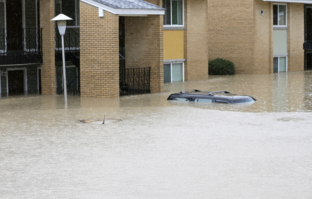 Floodwaters engulf cars at an apartment complex in Columbia, S.C., on Sunday.
