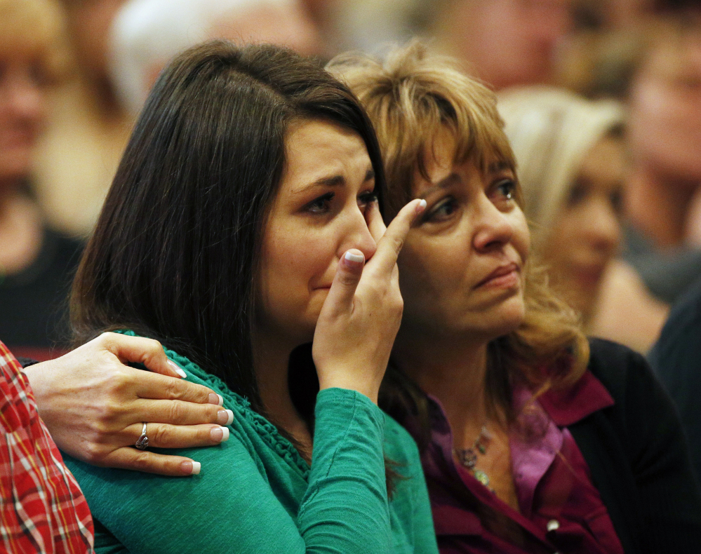 Lacey Scroggins, left, is comforted by her mother, Lisa Scroggins, during a church service Sunday in Roseburg, Ore.  The Associated Press
