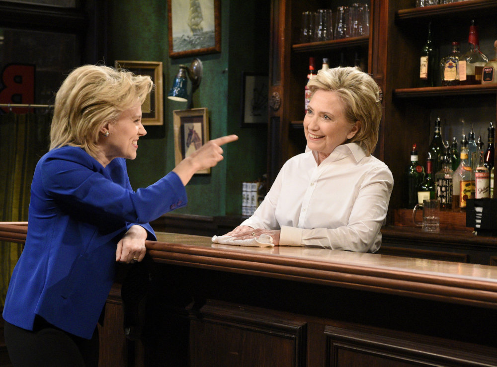 "Kate McKinnon, left, portrays Hillary Clinton, and Hillary Clinton, right, portrays Val, a bartender, during a sketch on ""Saturday Night Live"" in New York."