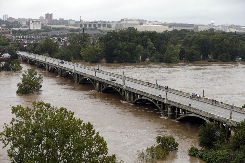 The Congaree River, swollen with floodwaters, flows under the Gervais Street bridge in West Columbia, S.C. in Columbia, S.C., Sunday, Oct. 4, 2015. Hundreds were rescued from fast-moving floodwaters Sunday in South Carolina as days of driving rain hit a dangerous crescendo that buckled buildings and roads, closed a major East Coast interstate route and threatened the drinking water supply for the capital city.