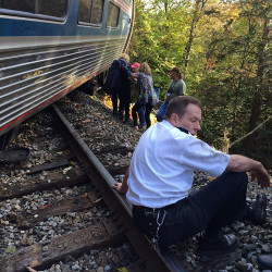 A train conductor sits next to an Amtrak train after it derailed Monday near Roxbury, Vt., about 20 miles southwest of Montpelier.