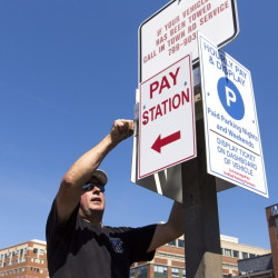 Ed Gagne installs signs last month at a private parking lot in Portland managed by Unified Parking Partners. The company has been under fire for its car-booting practices, but officials say their policy is fair and clearly spelled out.