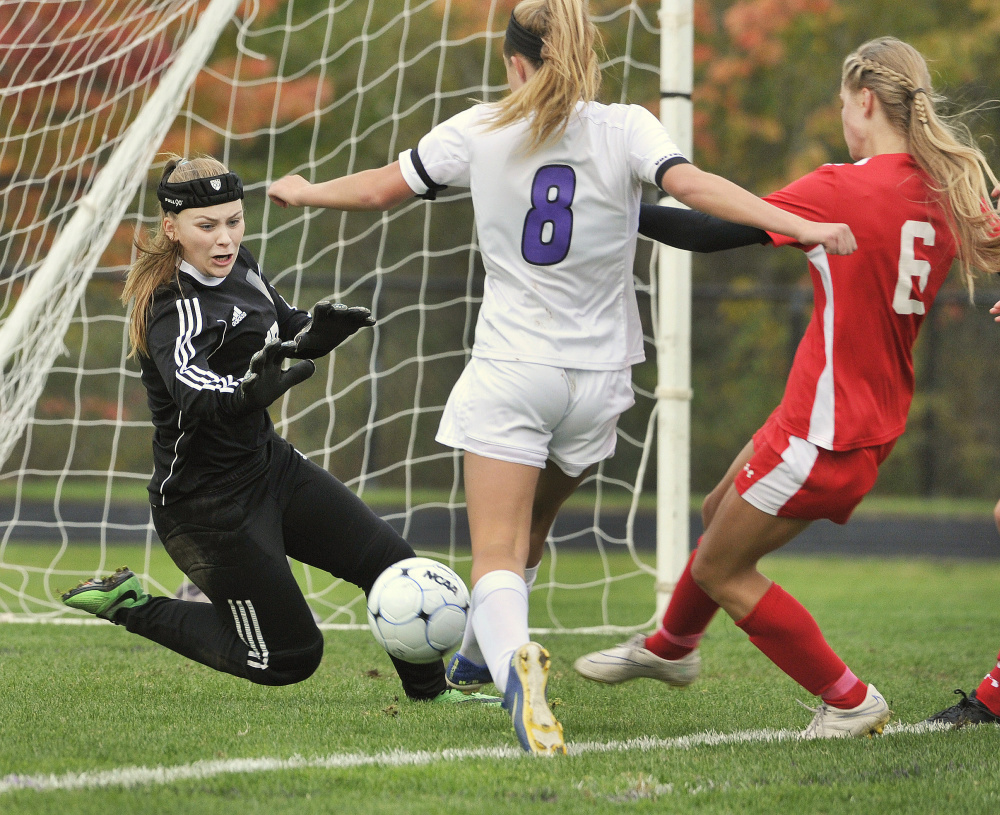 Sanford goalie Kyla Bragg makes a save on a shot by Marshwood's Reagan Nichols, center, while Sanford's Megan O'Connell defends during the Hawks' 3-1 win in a Class A South girls' soccer game Monday in South Berwick.