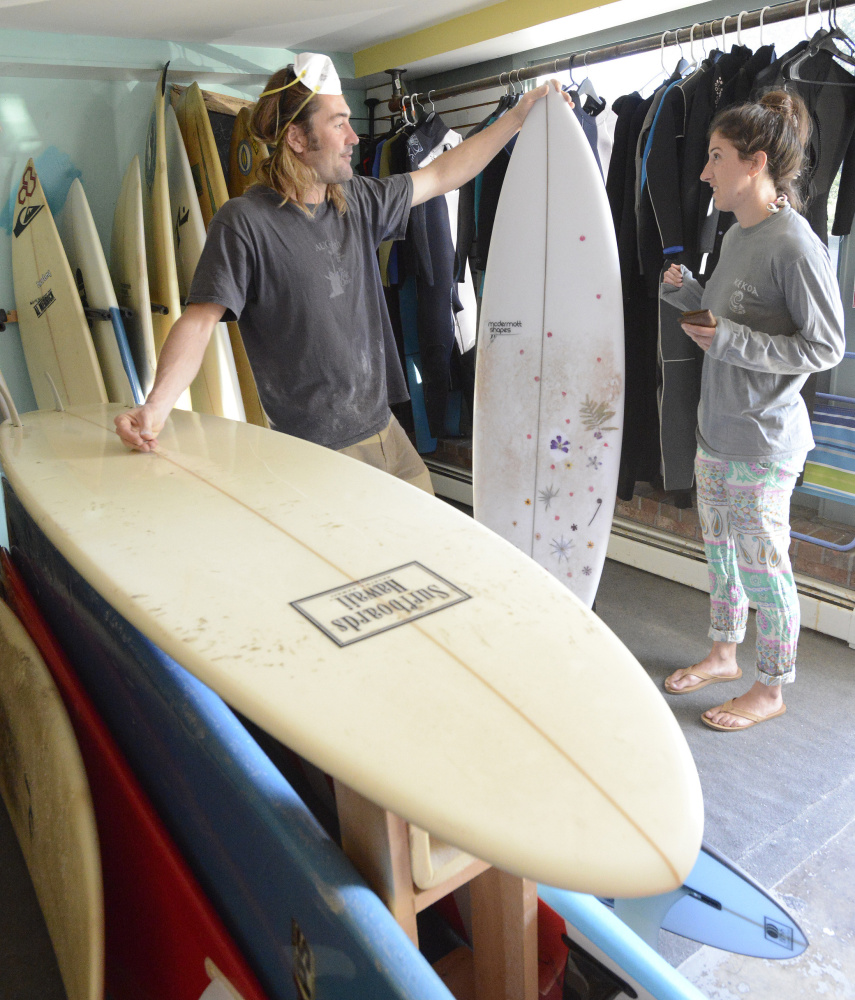 Andy McDermott talks with customer Margot Levy of Portland, whose custom surfboard was in the shop for a ding repair. Shawn Patrick Ouellette/Staff Photographer