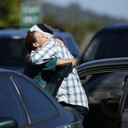 Student Mathew Downing, right, is comforted by an unidentified woman as they return to Umpqua Community College, Monday, in Roseburg, Ore.