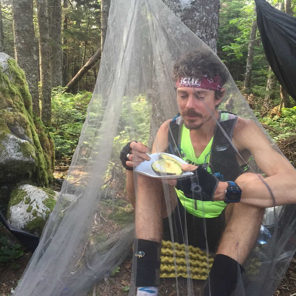 Scott Jurek snacks on avocados while in the Mahoosuc Range near the New Hampshire-Maine border. His wife and friends hiked 3 miles to bring him the treat.