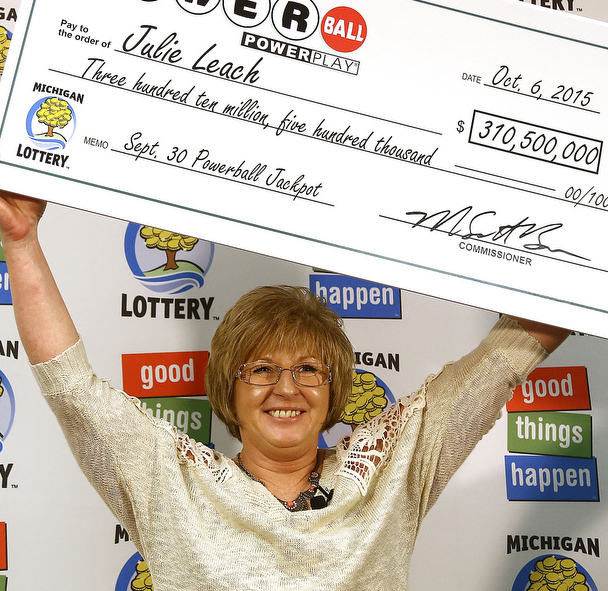 Powerball winner Julie Leach holds a ceremonial check for $310.5 million Tuesday.