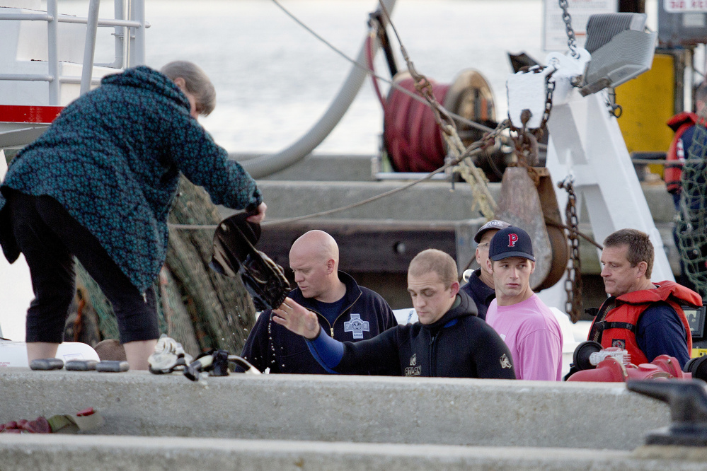 Members of the dive team hand up their gear after recovering the body of Dennis McGrath near the Portland Fish Pier on Wednesday.