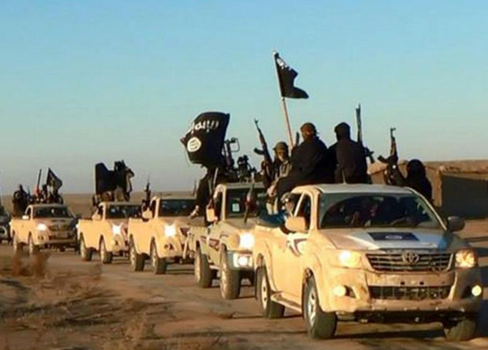 "Islamic State group militants ride in Toyota pickups in this photo released by a militant website. Toyota says its policy is to not sell vehicles ""for paramilitary or terrorist activities."""