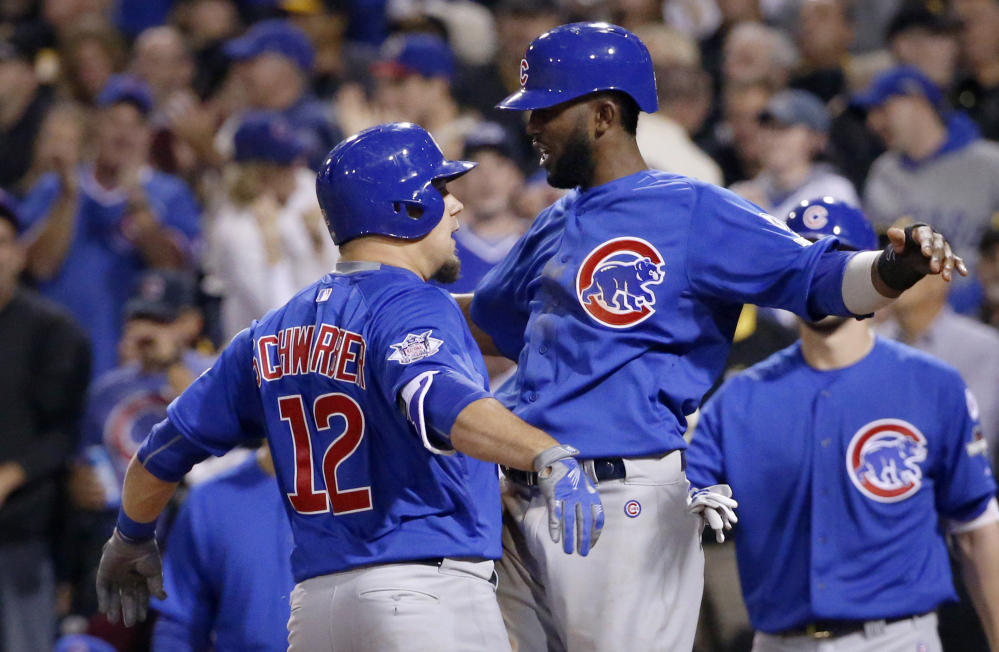 Chicago Cubs Kyle Schwarber (12) and Dexter Fowler celebrate after Schwarber drove in Fowler with a two-run home run in the third inning of Chicago's 4-0 win.