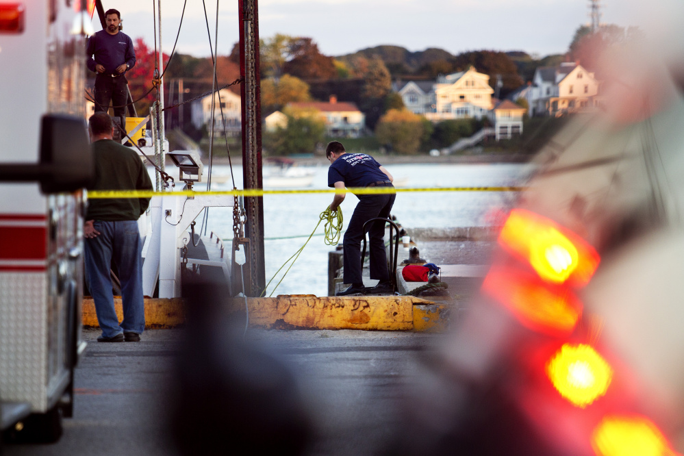 U.S. Coast Guard officials and other emergency personnel look for a diver Wednesday after he failed to surface while working under a fishing vessel at the Portland Fish Pier.