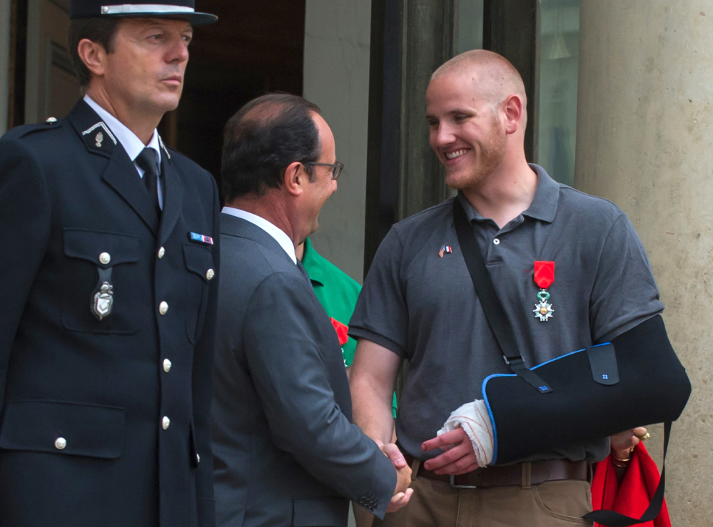 French President Francois Hollande shakes hands with U.S. Airman Spencer Stone outside the Elysee Palace in Paris after awarding Stone the French Legion of Honor.