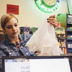 Colucci's Hilltop Superette cashier Ayriel Chase prepares a plastic bag for a customer in Portland the first week the bag fee was enacted.