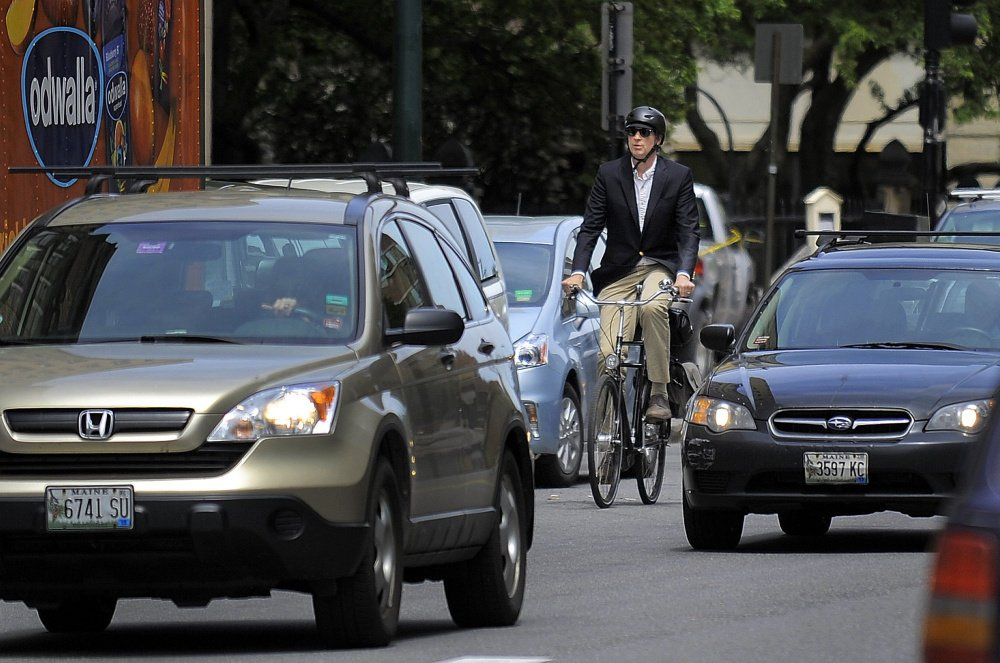 Bicyclists like this commuter on Congress Street in Portland will be subject, as will motorists, to a new Maine law taking effect Oct. 19 that could increase tickets that police issue for violations.