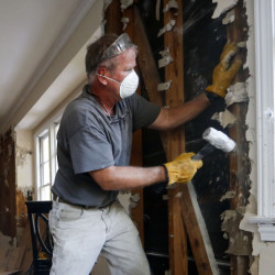 Bryan Allen works to remove wet drywall from a friend's flood-damaged home Thursday in Columbia, S.C. It could take until the weekend for the threat of flooding to ease.