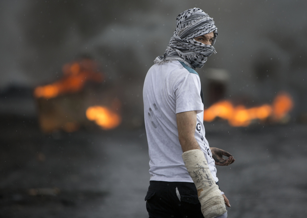 A Palestinian stands amid smoke from burning tires during clashes with Israeli troops near Ramallah on Thursday.