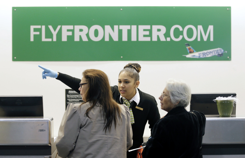 A Frontier Airlines employee directs passengers at Cleveland Hopkins International Airport. Much of the grousing about discount airlines is tied to dismal on-time records. Numerous fees and tightly packed seats also draw criticism.