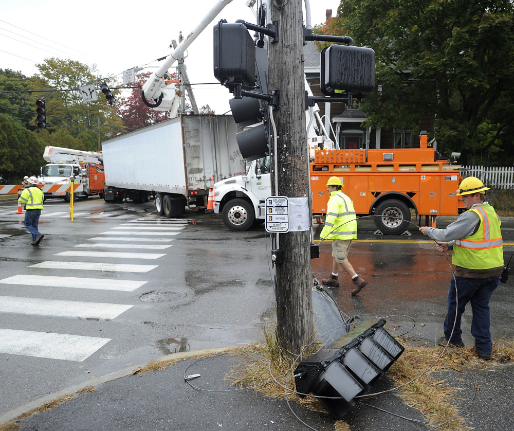 PORTLAND, ME - OCTOBER 9: Workers remove and contain the traffic lights that fell after a semi-tractor trailer truck snapped off at the corner of Brighton and Stevens Avenues. (Photo by Gordon Chibroski/Staff Photographer)