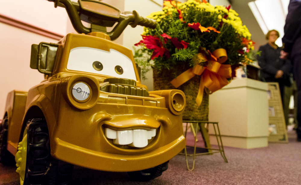 Toys, including this ride-on truck, were interspersed with more than a dozen flower arrangements at Fortin Funeral Home during a public wake Friday in Auburn in memory of Colton Guay, a 20-month-old boy who died after exposure to E. coli.