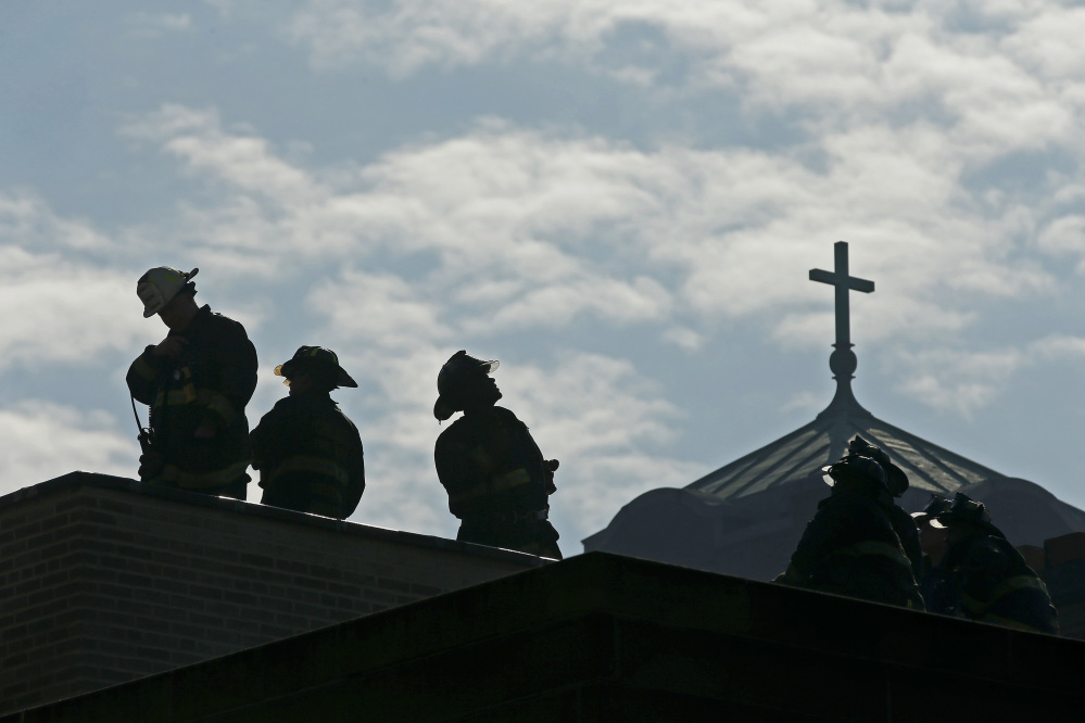 Chicago firefighters stand on a building next door to the Shrine of Christ the King Church at 64th Street and Woodlawn Avenue in Chicago as crews clean up and hose down the building on Wednesday. Jose M. Osorio/Chicago Tribune/TNS