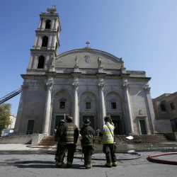 Chicago firefighters pause outside the Shrine of Christ the King Church in the city's Woodlawn area after an extra-alarm fire Wednesday caused extensive damage. Dozens of women and children were evacuated from the shelter next door. (Jose M. Osorio/Chicago Tribune/TNS)