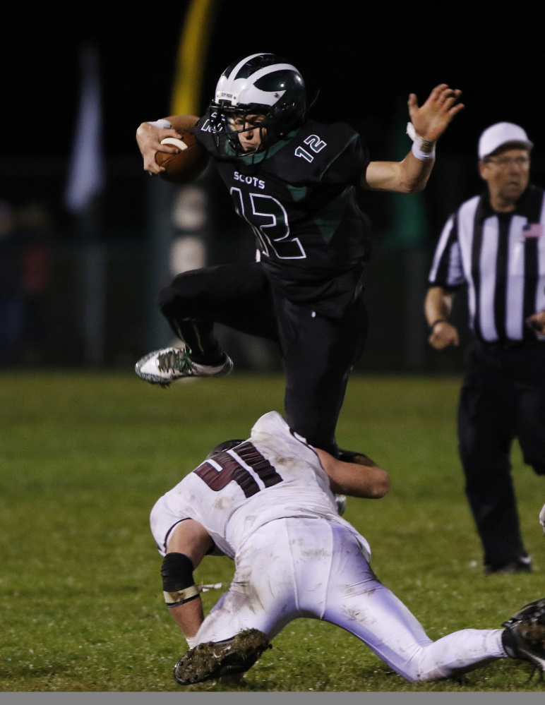 Bonny Eagle quarterback Cam Day jumps over Windham's Patrick Leavitt during the third quarter of their game in Standish on Friday night. Day helped lead the Scots to a 33-13 win. Joel Page/Staff Photographer