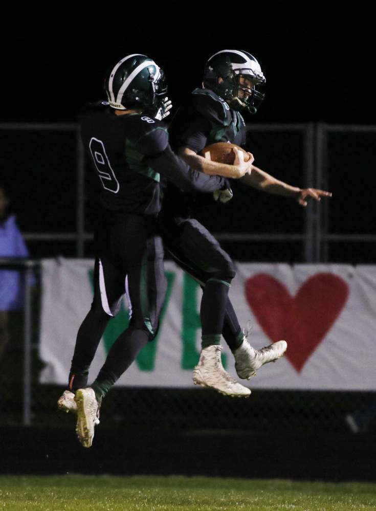 Bonny Eagle's Ben Autry, left, celebrates with Eben Cram in the second quarter following the first of Cram's two receiving touchdowns Friday night in a 33-13 win over Windham at Standish. Joel Page/Staff Photographer
