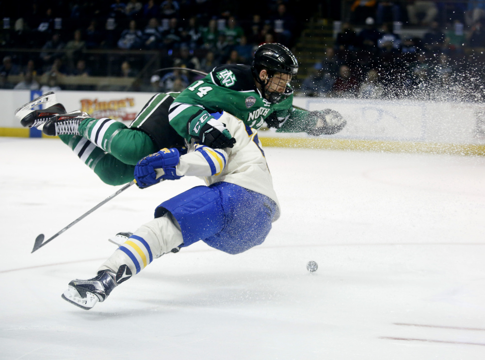 Austin Poganski of North Dakota gets upended by Owen Headrick of Lake Superior State during the second period of Friday's game at the Cross Insurance Arena. Shortly after this play, Poganski scored to give North Dakota a 3-2 lead.