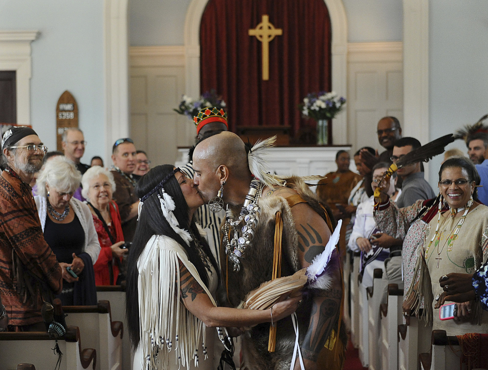 """StrongMedicine Bear kisses his new wife, WarriorWoman, after their wedding Sept. 26 at Eliot Church in Natick, Mass. """"To stand here, to get married here, where John Eliot preached, where my ancestors worshipped, is extremely meaningful,"""" he said."""