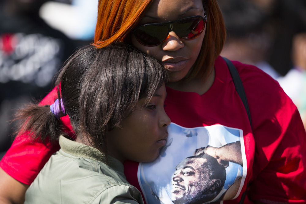 Margaret Holland of Baltimore hugs her daughter Jaylah Sabb, 9. Women were among those not invited to the original march.