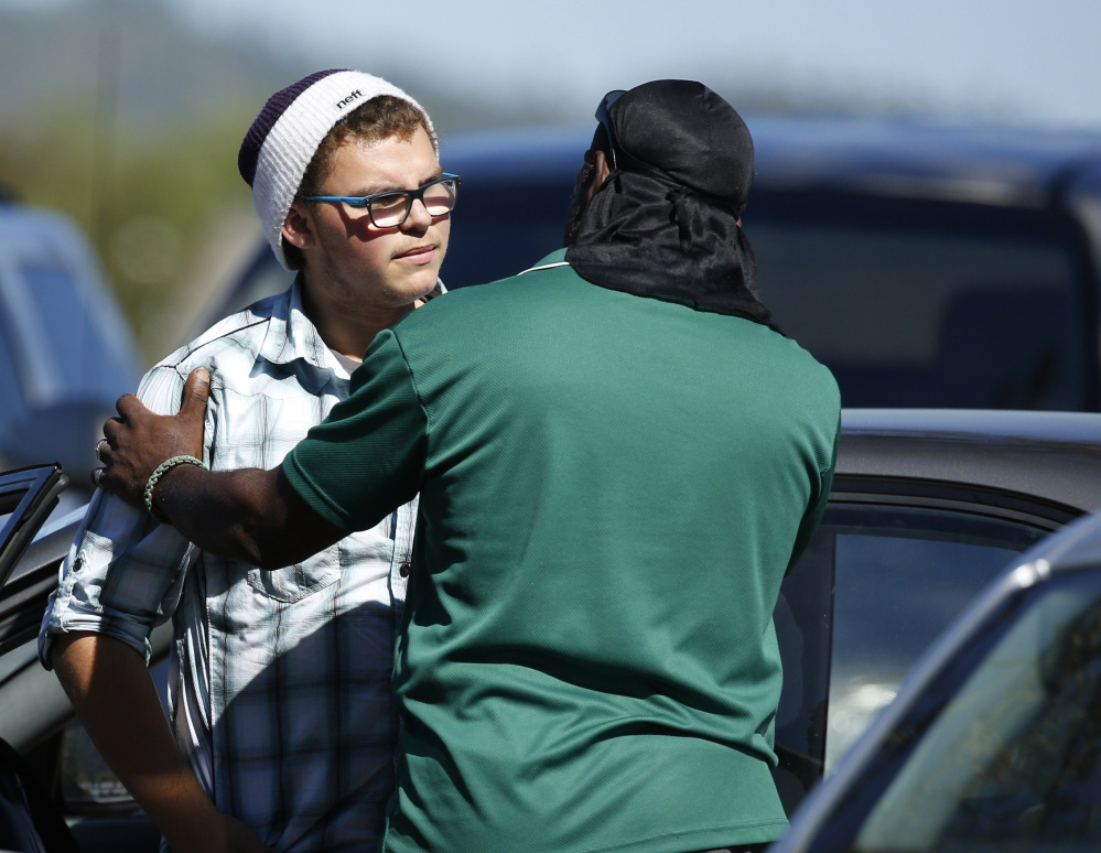 Student Mathew Downing, left, is comforted by an unidentified man Monday as they return to Umpqua Community College in Roseburg, Ore.