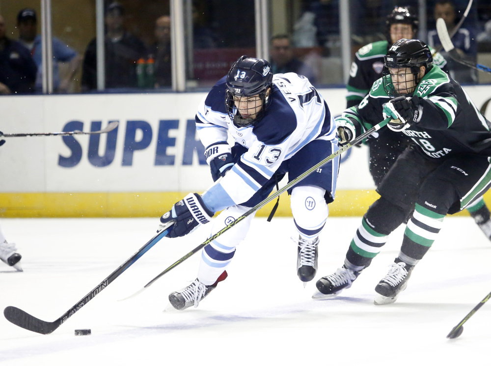 Nolan Vesey of Maine works to bring the puck up the ice while being pursued by Chris Wilkie of North Dakota in the final game of the Ice Breaker tournament at the Cross Insurance Arena.