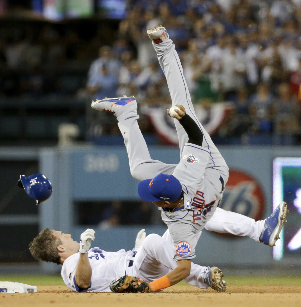 Mets shortstop Ruben Tejada goes over the top of Dodgers second baseman Chase Utley in the seventh inning Saturday. Tejada broke his leg on the play.