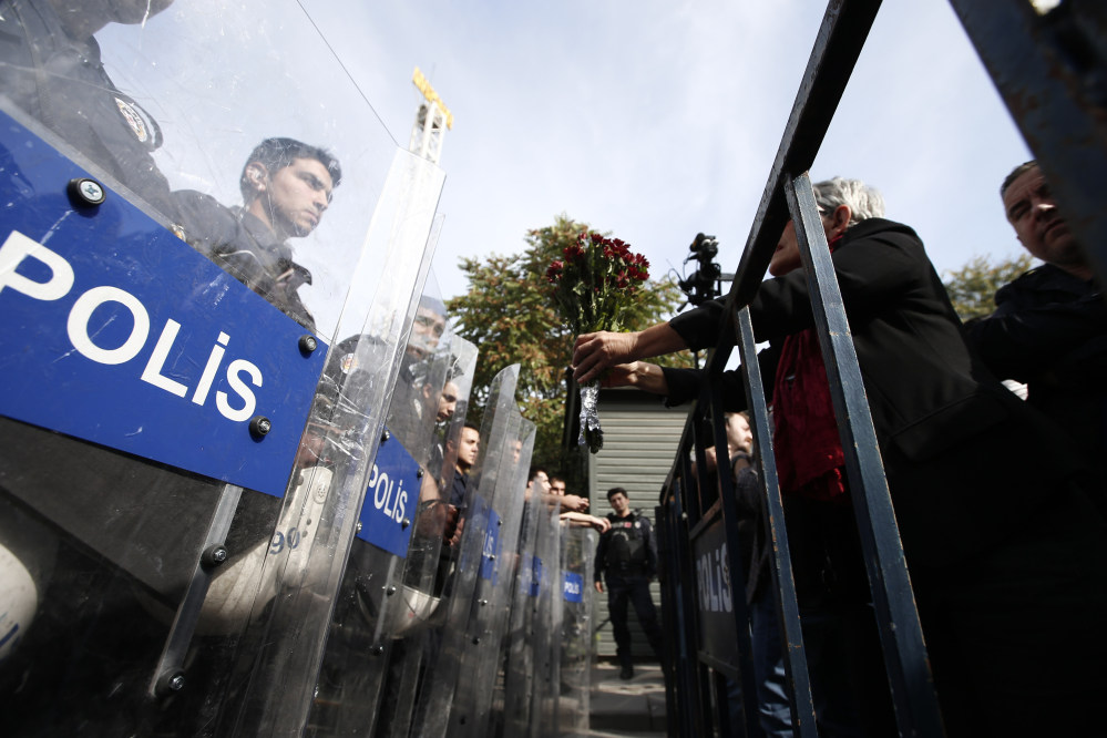 A protester offers carnations to Turkish police blocking the way to the site of Saturday's  explosions in Ankara, Turkey, on Sunday. Scuffles broke out as police prevented pro-Kurdish politicians and other mourners from laying carnations at the site of two suspected suicide bombings that killed 95 people and wounded hundreds in Turkey's deadliest attack in years. Police insisted investigators were still working at the site.