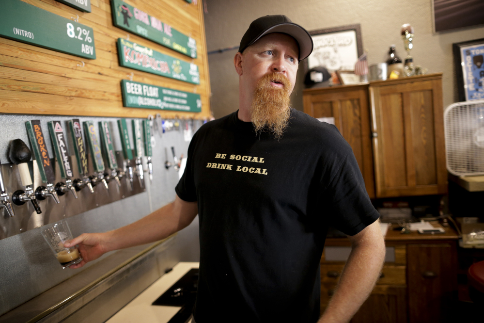 Beer brewer Chuck McLaughlin pours a beer for a client at his Fallbrook Brewing Co. brewery in Fallbrook, Calif. Amid California's severe drought and tough new local water restrictions, McLaughlin has had to get creative to continue brewing his craft beers.