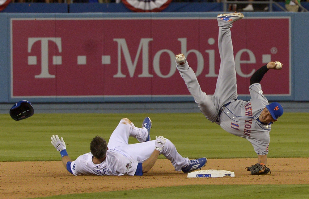 Mets shortstop Ruben Tejada falls after a slide by Chase Utley of the Dodgers in the seventh inning of an NL division series Saturday in Los Angeles.