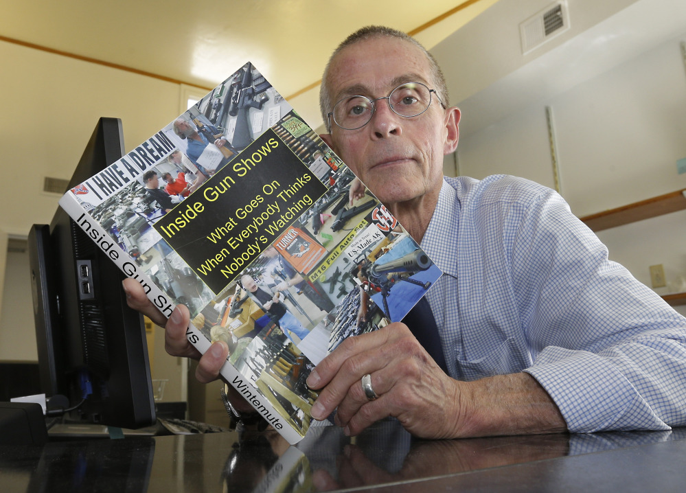 In this Oct. 6, 2015 photo, Dr. Garen Wintemute poses with a copy of a study he did on gun shows, at his office at the University of California Davis Medical Center in Sacramento, Calif. Wintemute, an emergency doctor, who is board certified in family practice, is a long-time national leader in gun violence, having researched gun accessibility, connections between gun ownership and violence.