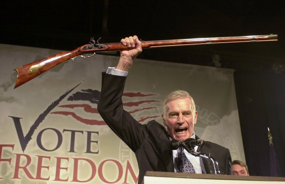 "National Rifle Association President Charlton Heston holds up a rifle as he addresses gun owners during a ""get-out-the-vote"" rally in Manchester, N.H., in October 2002."