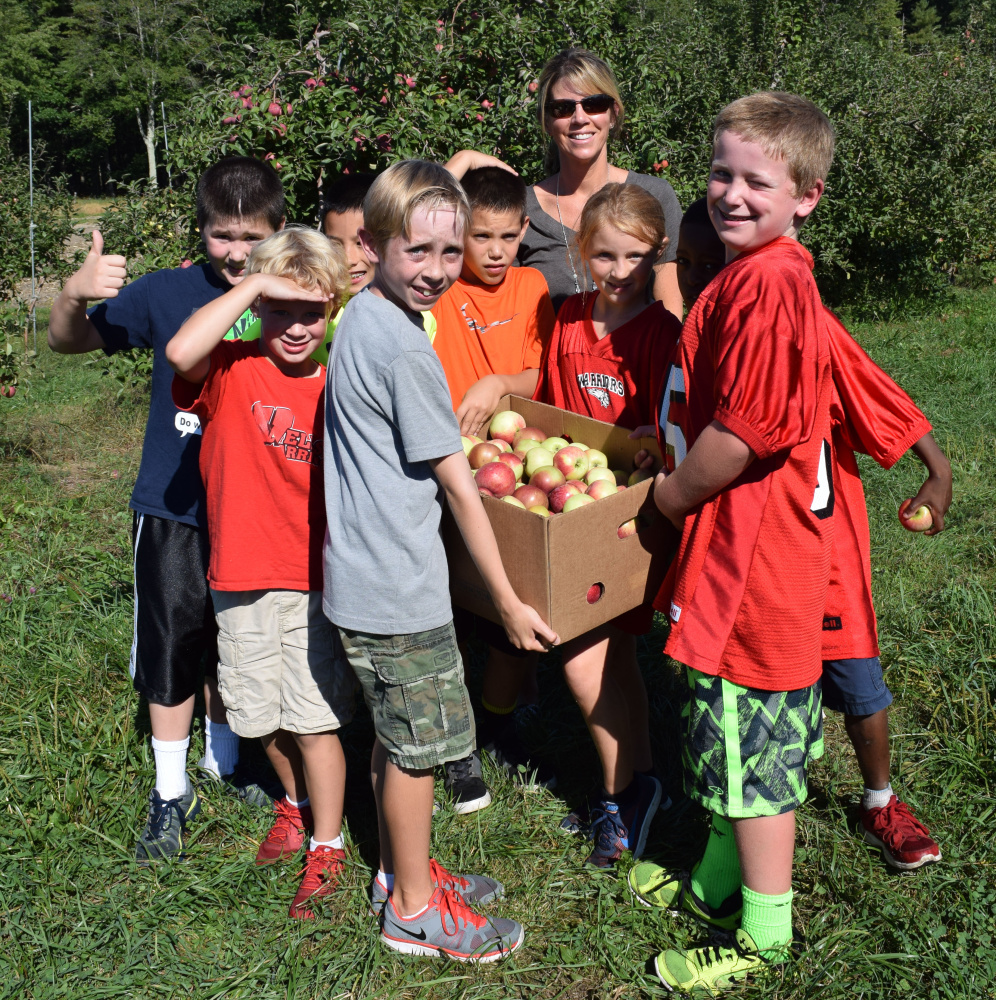 Wells Elementary School teacher Melissa Stapleton and students carry one of the boxes of apples they harvested at Spiller Farm in Wells as part of Farm to School Week.