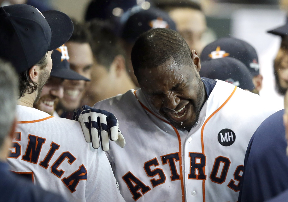 Teammates splash water on Houston Astros' Chris Carter in the dugout after he hit a home run against the Kansas City Royals in the seventh inning in Game 3 of the American League Division Series on Sunday in Houston. The Associated Press