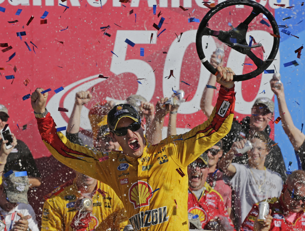 Joey Logano celebrates after earning his fourth Sprint Cup win of the season Sunday at Charlotte Motor Speedway. Logano led 227 of 334 laps, and is assured of being one of the final eight drivers in the playoffs.