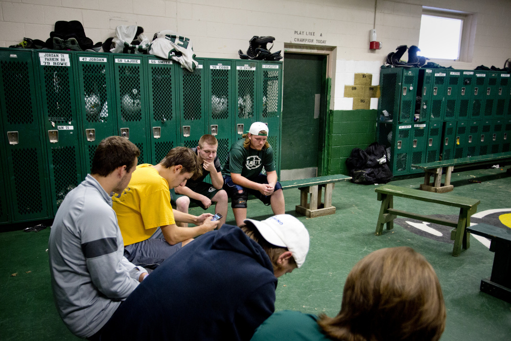 "Members of the Leavitt Area High School football team sit quietly in their locker room in Turner before practice Monday as the conversation shifted to teammate Adam Smith, who suffered a severe spleen injury on Saturday. ""I can't even believe this is real,"" said senior defensive lineman Gage Jordan, center, with hand on his chin."