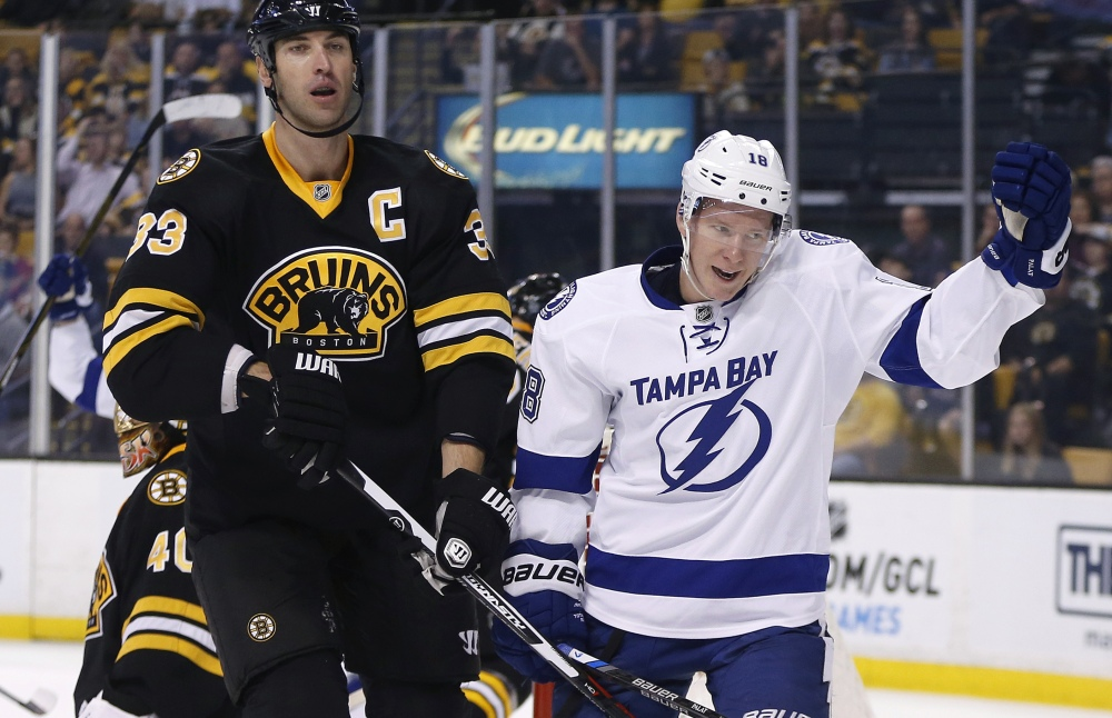 Tampa Bay's Ondrej Palat celebrates beside Boston defenseman Zdeno Chara after scoring in the first period of Monday's game in Boston.
